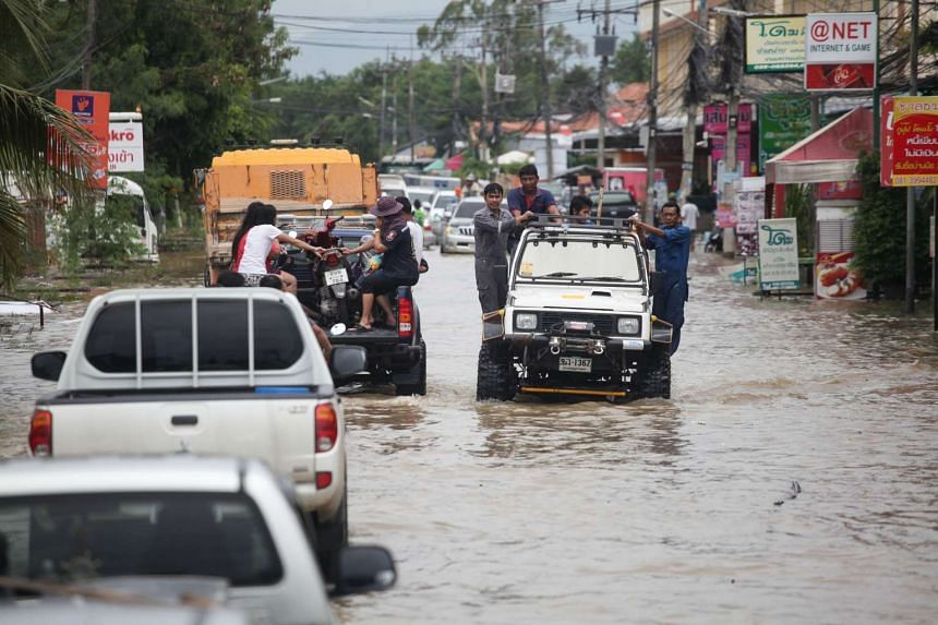 Rayong residents travelling on flooded roads, which have led to traffic chaos in many of the affected areas.