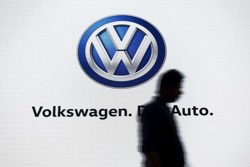 A man walks past a screen displaying the Volkswagen logo.