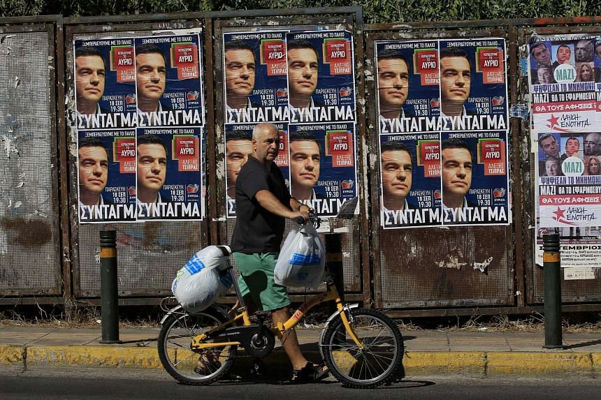 A man pushes his bicycle past pre-election posters of SYRIZA party and former Prime Minister Alexis Tsipras, in Athens, Greece, on Sept 18, 2015. Elections are being held on September 20, 2015, after prime minister Tsipras resigned on August 20, 2015