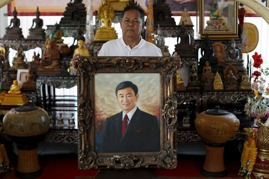 """Red shirt movement leader Kwanchai Praipana poses with a photo of former PM Thaksin Shinawatra at his office in Udon Thani, Thailand, September 15, 2015. From self-imposed exile, the influential leader of Thailand's rural """"red shirt"""" opposition move"""