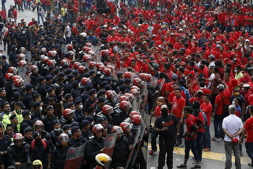 """Riot police blocking the entrance to Chinatown from """"red shirt"""" demonstrators, during the rally supporting PM Najib last Wednesday."""