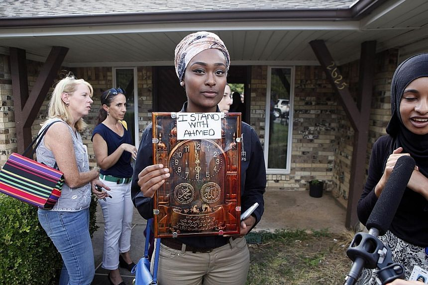 A student in Irving (above centre), Texas, holding a sign in support of teenager Ahmed Mohamed, who was arrested after a high school teacher thought that a homemade clock he brought to class was a bomb, and called the police. This led outraged Netize