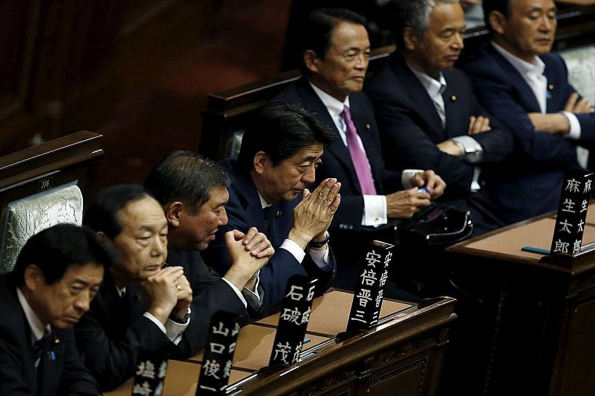 Mr Shinzo Abe (fourth from left), with his Cabinet members in the Lower House of Parliament in Tokyo last Friday. His government pushed through contentious legislation allowing troops to fight abroad for the first time since World War II despite publ