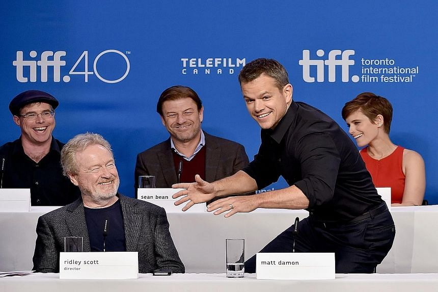 Ridley Scott (second from left) directs The Martian written by Andy Weir (left, behind Scott), which stars Matt Damon (second from right), Sean Bean (centre) and Kate Mara (right).