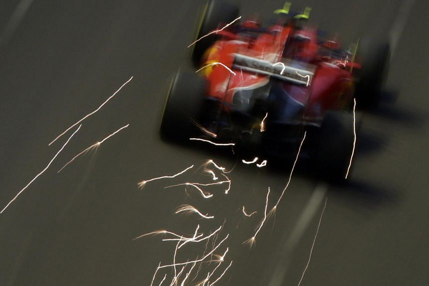 A shower of sparks emerging from the Ferrari of Kimi Raikkonen during first practice at the Marina Bay Street Circuit as seen from Swissotel The Stamford on Friday. The enduring appeal of the sparks was part of the reason for the reintroduction of ti
