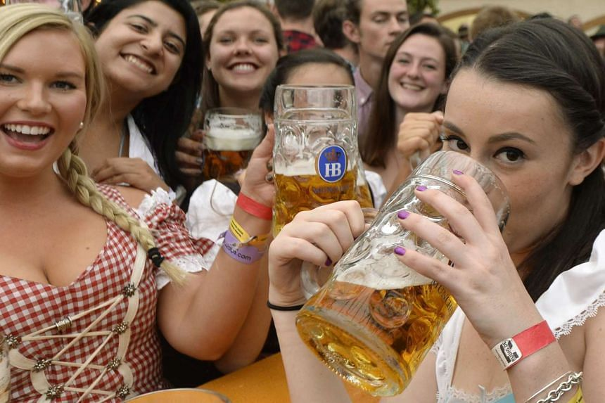 Visitors to the Oktoberfest beer festival have the first beers after the festival's opening in Munich, southern Germany.