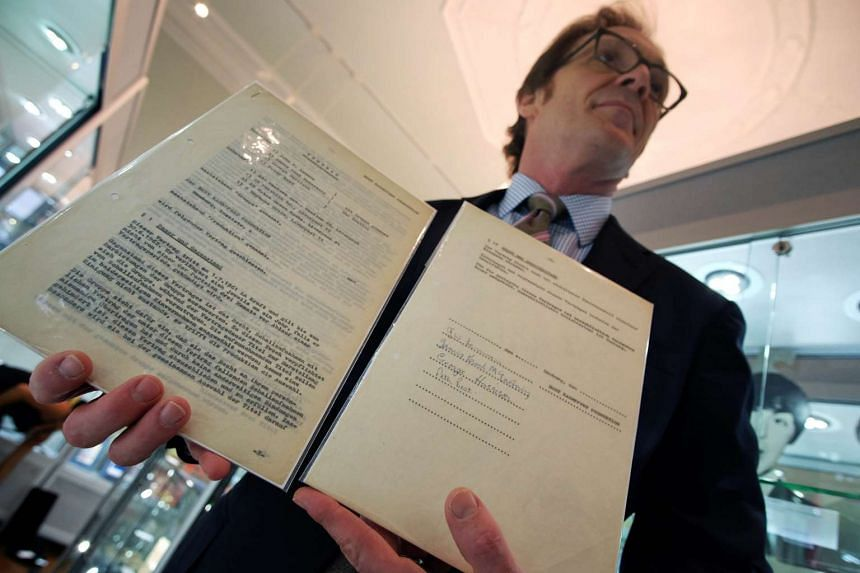 Heritage Auctions' Dean Harmeyer displays the first-ever recording contract signed by The Beatles.