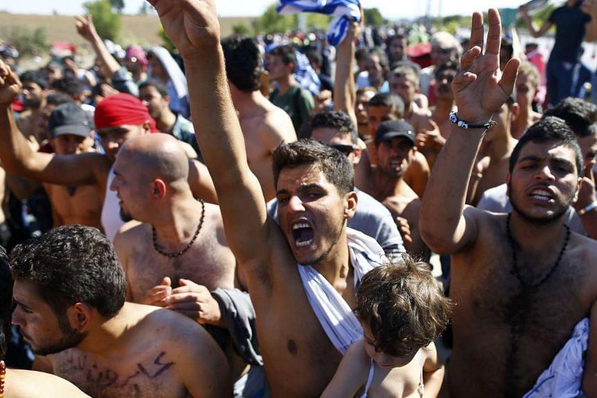 Migrants react as Turkish police and gendarmes block migrants on a highway near Edirne, Turkey.