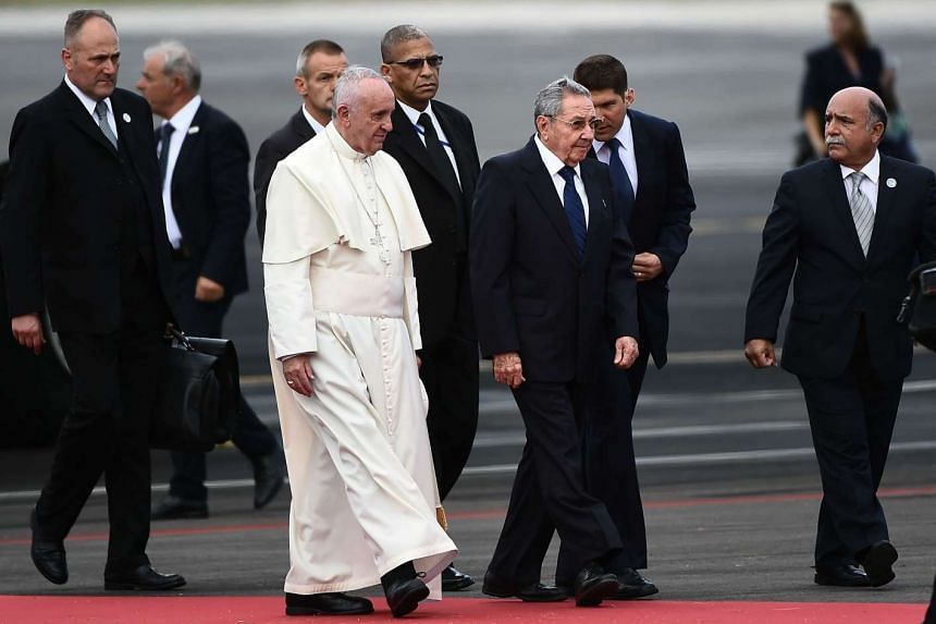 Pope Francis (centre left) is welcomed by Cuban President Raul Castro (centre right) upon landing in Havana.