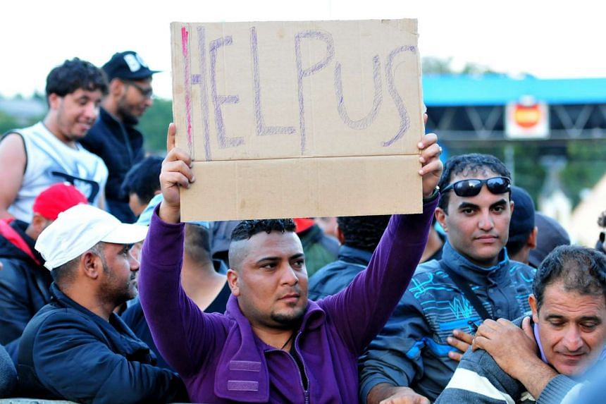 """Migrants hold a """"Help us"""" placard as they wait at the border crossing between Rigonce in Slovenia and Hamica in Croatia on Sept 19, 2015."""