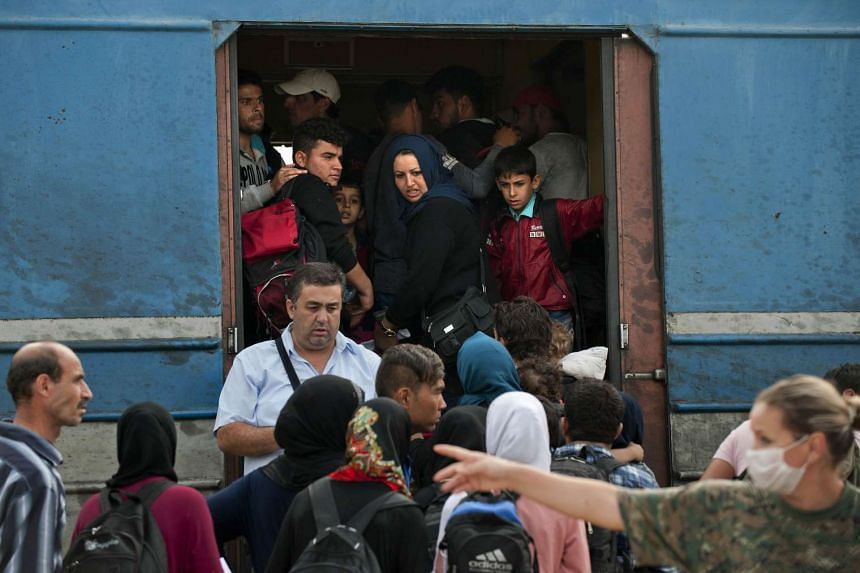 Refugees board a train heading to Serbia near the town of Gevgelija, at the border line between Greece and Macedonia, on Sept 20, 2015.