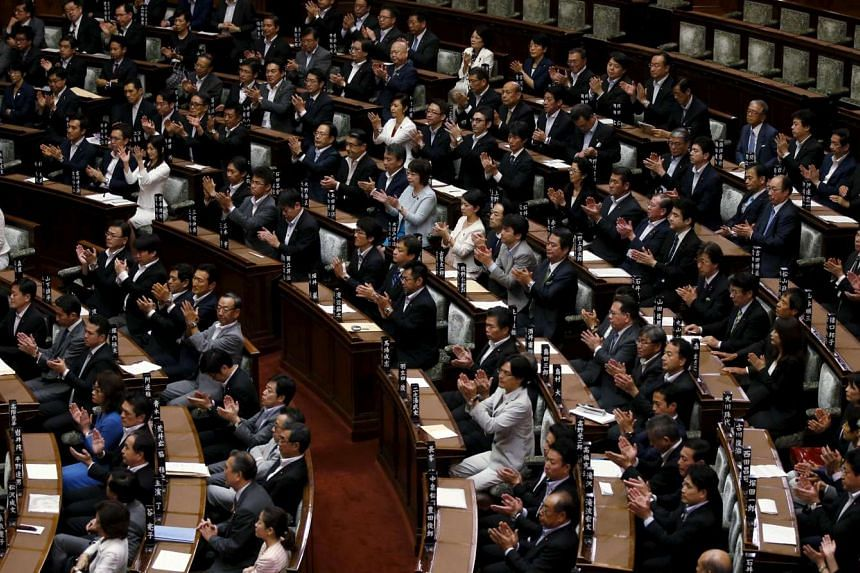 Ruling party's lawmakers clap their hands after the upper house of Japan's parliament approve security bills during the plenary session at the Upper House of the parliament in Tokyo, Japan, on Sept 19, 2015.