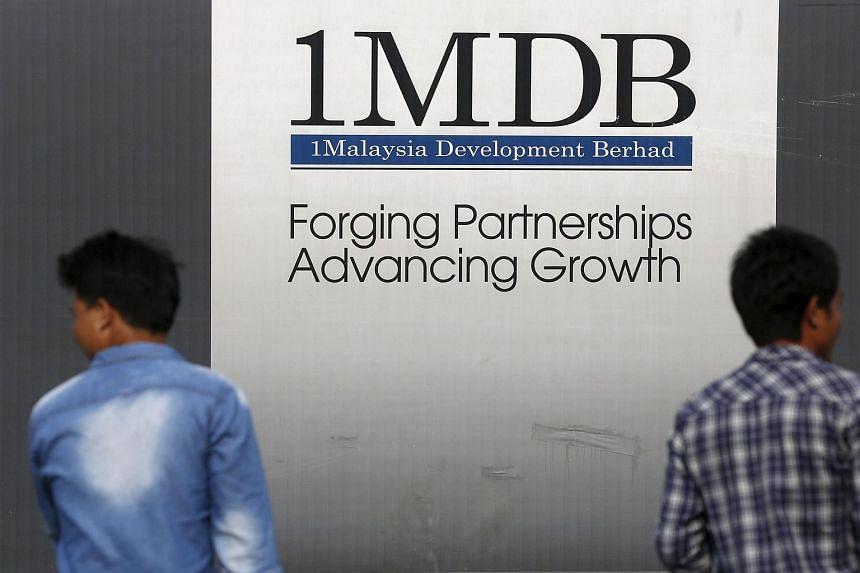 Men walk past a 1 Malaysia Development Berhad (1MDB) billboard.