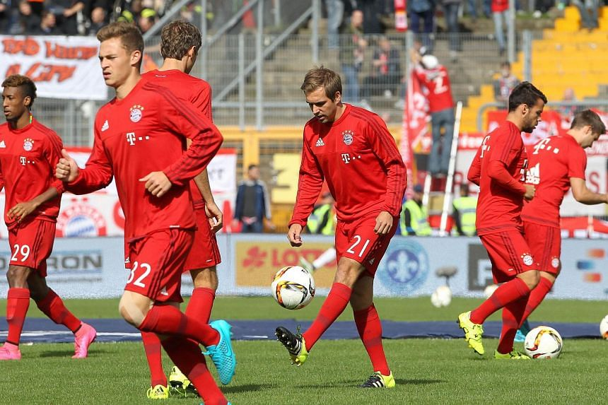Munich's players including Bayern Munich's defender Philipp Lahm (center) warm up prior to the German first division Bundesliga football match SV Darmstadt 98 vs FC Bayern Munich, in Darmstadt, southern Germany on Sept 19, 2015.