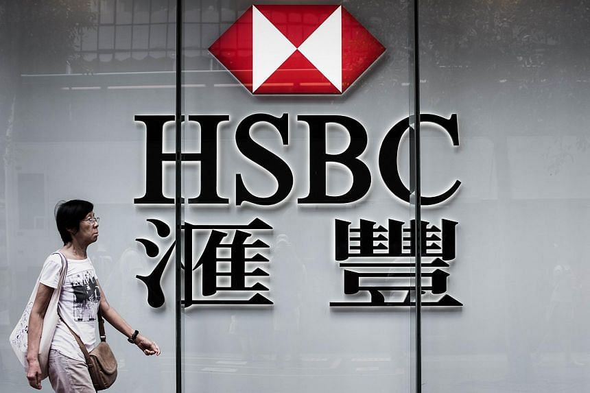 A woman walks past a logo of the HSBC bank in Hong Kong on Aug 3, 2015.