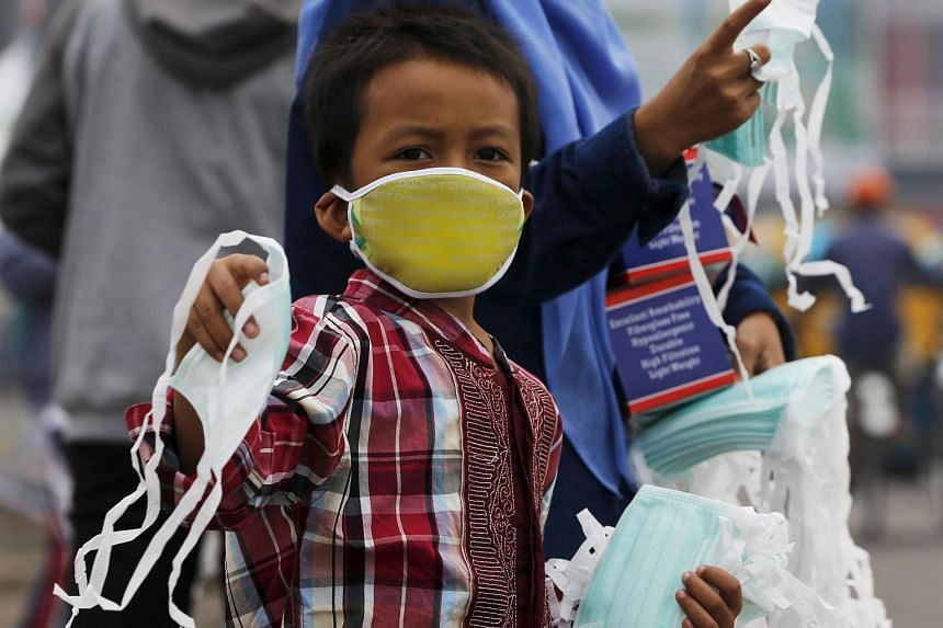 A child offers face masks to people along a haze shrouded street in Palembang, on the Indonesian island of Sumatra, on Sept 20, 2015.