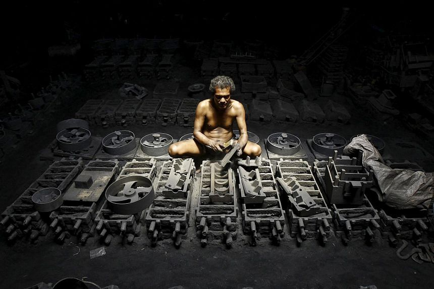 A labourer works inside the manufacturing unit of iron parts at a factory on the outskirts of Kolkata, India, on  Sept 11, 2015.
