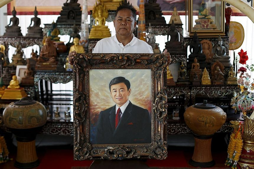 Red-shirt leader Kwanchai Praipana posing with a painting of former PM Thaksin in his office in Udon Thani. Mr Kwanchai was shot in the arm in a drive-by shooting at his rural home when Bangkok was paralysed by protests preceding last year's coup.