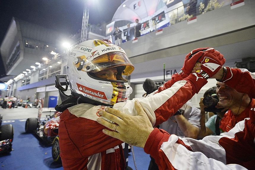 A jubilant Sebastian Vettel celebrates with the Ferrari team after his win last night. Before taking his place on the podium, he bent down to kiss the car that carried him to victory.