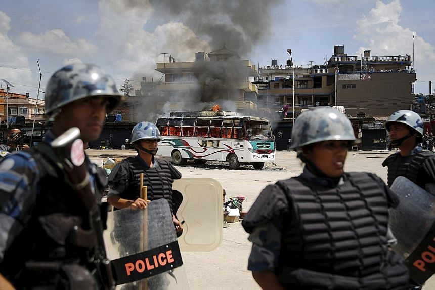 Members of the Nepalese Armed Police Force in front of a bus set on fire by protesters in Kathmandu yesterday. Weeks of clashes with the police over the new Constitution have left more than 40 people dead.