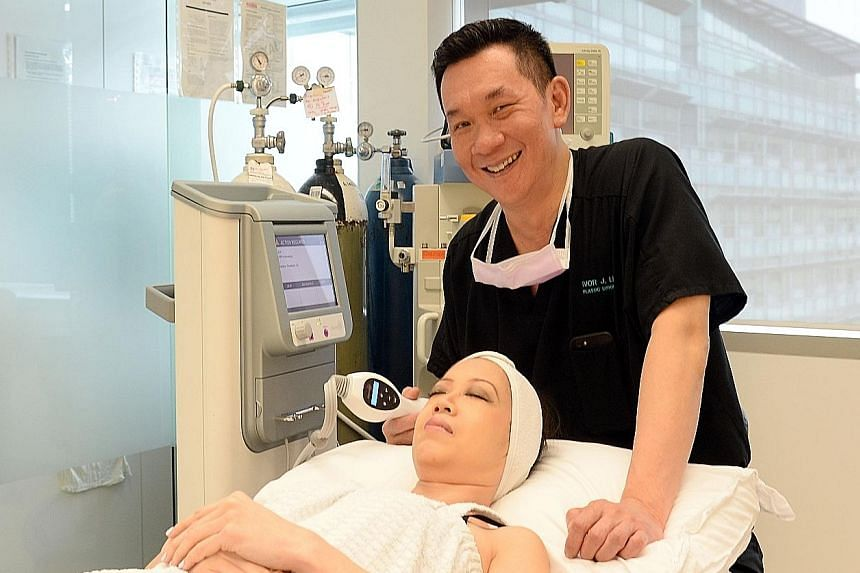 Dr Ivor Lim, with a member of his staff and a genuine Thermage machine, showing how treatment is carried out. A genuine machine costs more than $80,000 while a fake one goes for between $18,000 and $38,000.