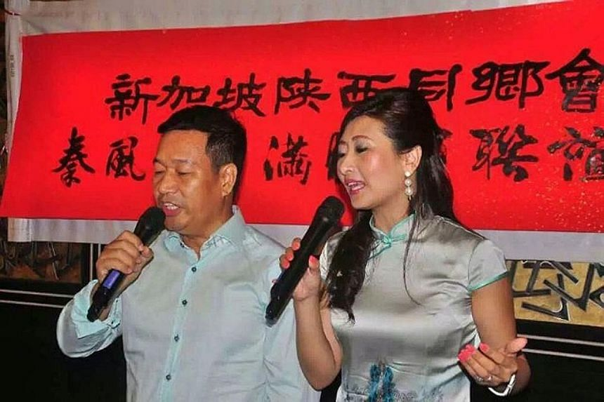 A giant lantern (above) being released into the sky at Kwong Wai Siu Hospital's mid-autumn celebration on its grounds last Saturday. Shaanxi Association president Zhao Bingli (left) and his wife, Shuran, singing at the clan's first Mid-Autumn Festiva