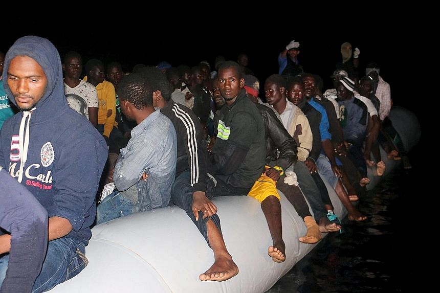 Migrants crowd onto a rubber dinghy in which they hope to reach Europe, after being detained at a Libyan navy base in the coastal city of Tripoli yesterday.