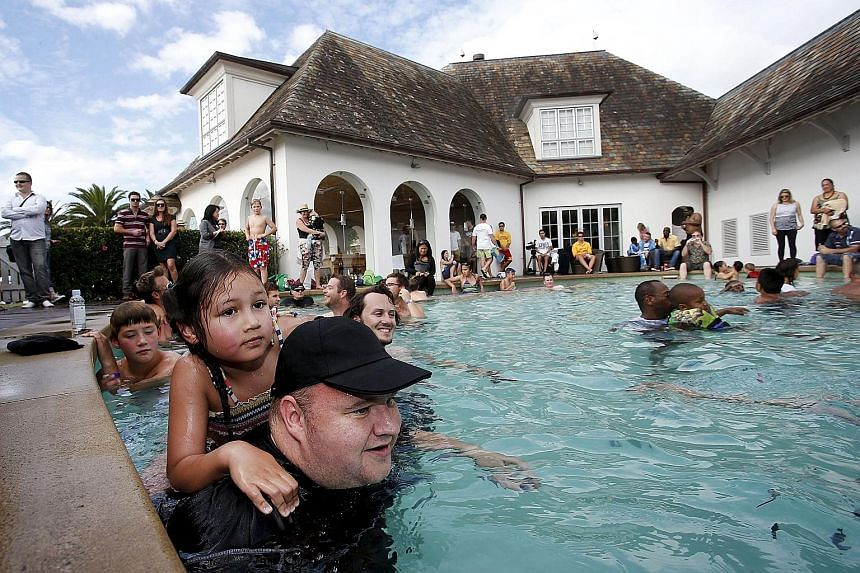 Kim Dotcom swimming with his daughter Kaylo at a pool party at his mansion in Auckland last year. The US says Dotcom and three co-accused Megaupload executives cost US film studios and record companies more than US$500 million by encouraging paying u