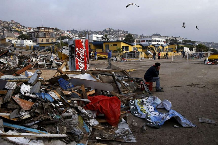 A resident sits next to debris at Coquimbo city in the north of Santiago after an earthquake hit areas of central Chile on Sept 18, 2015.