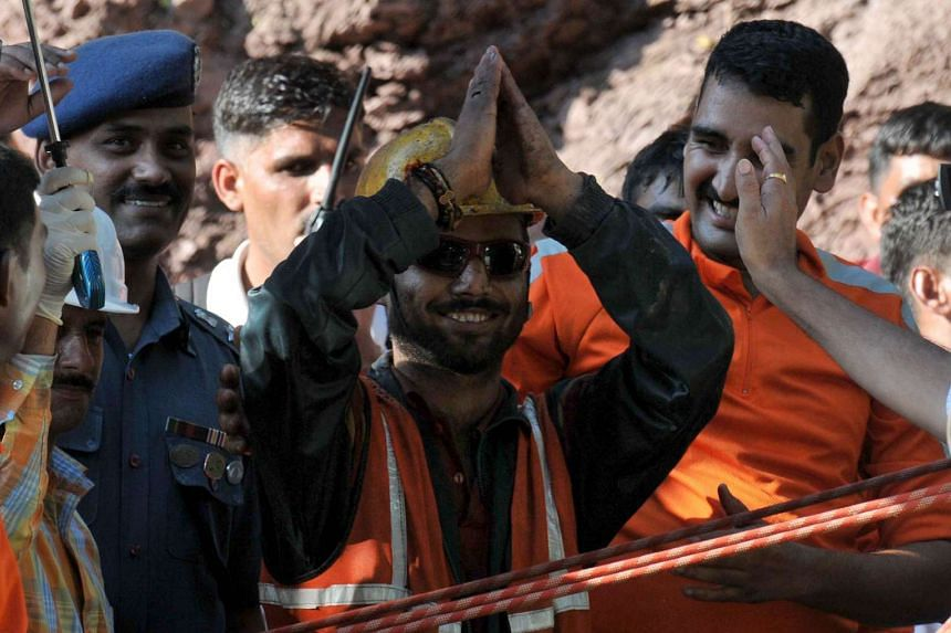 Indian worker, Satish Tomar (centre) gestures following his rescue after being trapped for close to nine days in a collapsed tunnel at Tihra, in Bilaspur district of northern Himachal Pradesh state on Sept 21, 2015.