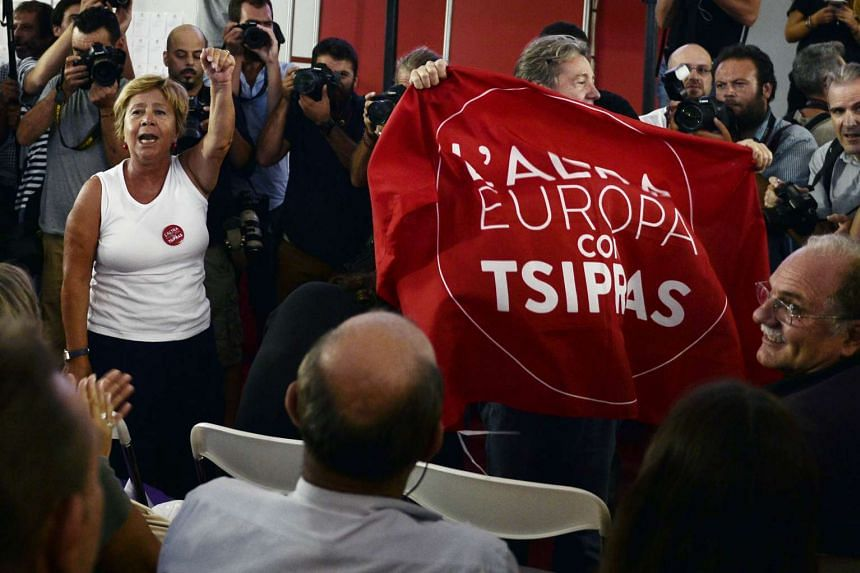 Syriza supporters react at the announcement of exit polls in Athens on Sunday  showing left-wing leader Alexis Tsipras winning the Greece election.