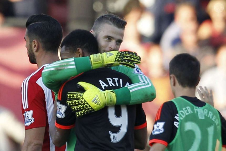 Manchester United's Spanish goalkeeper David de Gea embraces Manchester United's French striker Anthony Martial (second from left) after Manchester beat Southampton at St Mary's stadium on Sunday.
