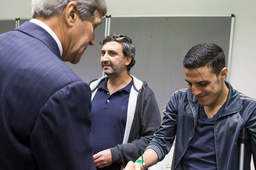 US Secretary of State John Kerry (left) talks with a man injured in a bomb attack in Syria during a meeting with a group of refugees fleeing Syria at Villa Borsig in Berlin on Sunday.