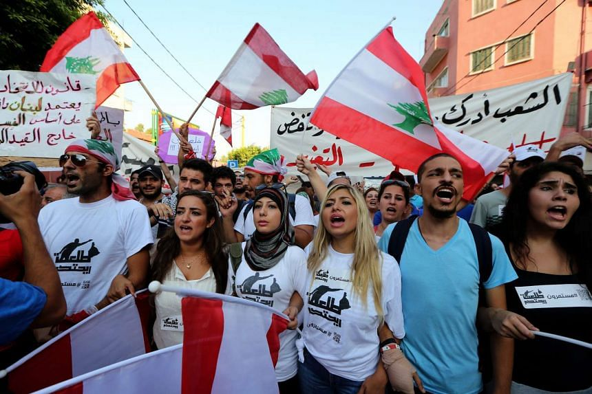 Lebanese anti-government activists wave Lebanese flags and banners with the Arabic words for 'You stink' as they march from Bourj Hamoud to downtown of Beirut and shout slogans against the Lebanese regime on Sunday.
