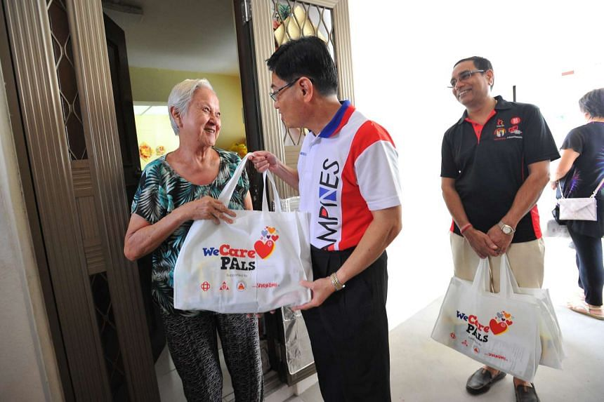 Mr Heng Swee Keat giving a WeCare welfare pack to retiree Wong Shiew Choo, 80, during the distribution of the packs with grassroots leaders and resident volunteers in Tampines GRC yesterday.