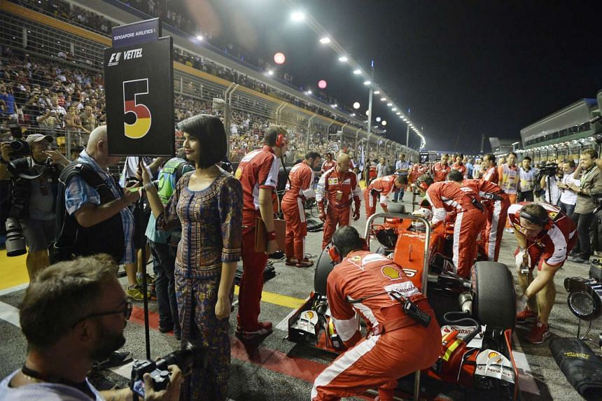 A Singapore Girl holding up Sebastian Vettel's pole position placard as the teams get ready for the start.