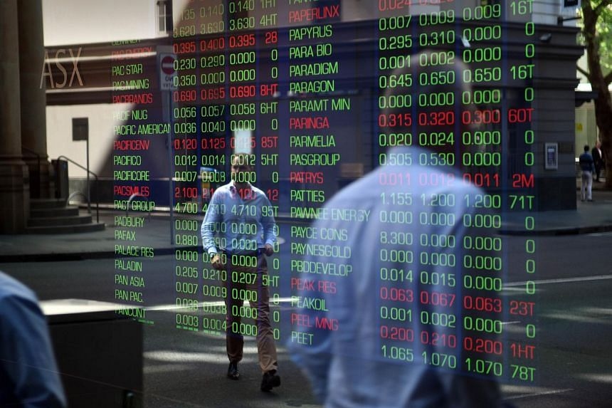 Passersby are reflected in the window of the Sydney Stock Exchange on Sept 18, 2015.
