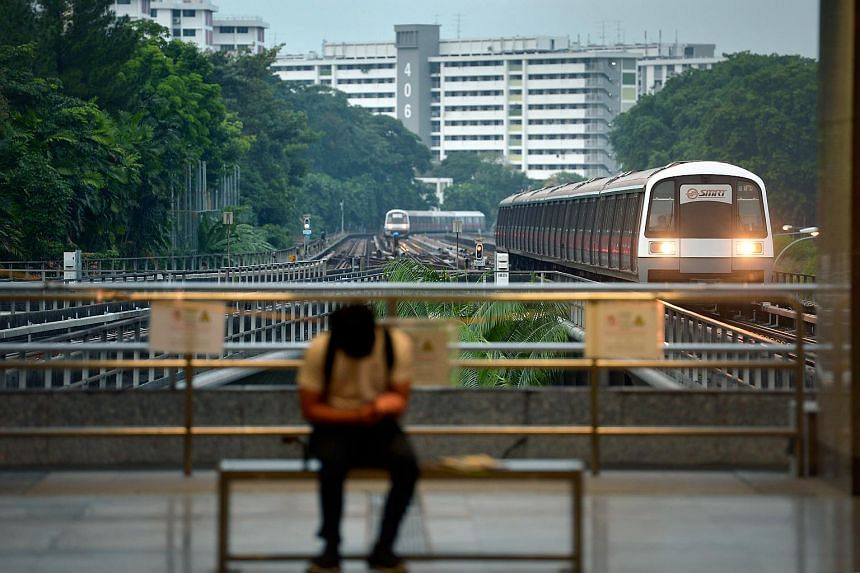 A commuter waiting on the platform as a MRT train arrives at Ang Mo Kio station on July 8, 2015.
