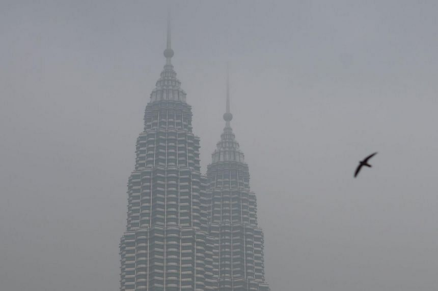 A bird flies as Malaysia's iconic Petronas Twin Towers are seen shrouded by haze in Kuala Lumpur on Sept 15, 2015.