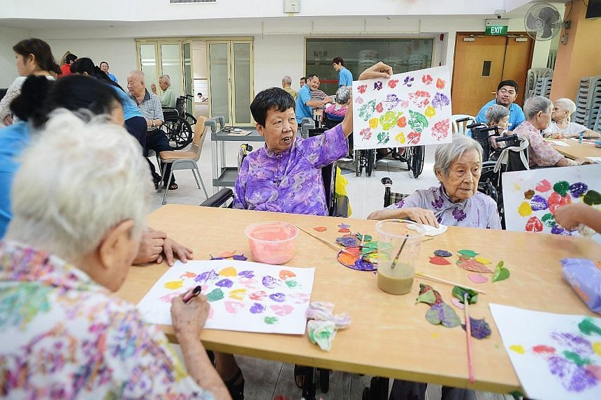 Ms Juan Po Giok (centre), 65, enjoying a visual arts session at the Ling Kwang Home for Senior Citizens last month. The former seamstress has attended several such sessions as she likes working with her hands.