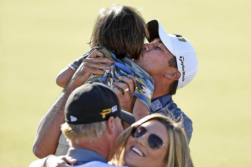 Jason Day holds his son Dash while wife Ellie hugs caddie Colin Swatten after the red-hot golfer bags his fourth title in his last six events, at the BMW Championship.