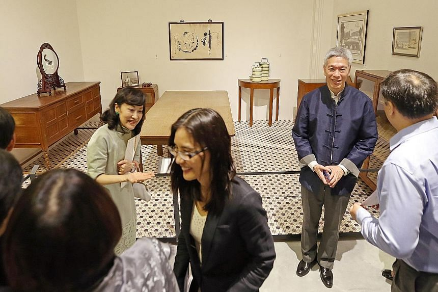 Mr Lee Hsien Yang (second from right), with his wife (second from left) Lee Suet Fern, explaining to guests the uses and significance of furniture and exhibits from Mr Lee Kuan Yew's house at the preview of the exhibition. Guests at the preview of th