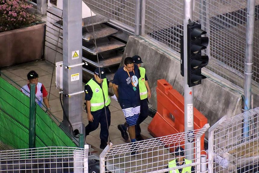 A man being led away after invading the track during the Singapore Grand Prix on Sunday. He has been arrested and is assisting police with investigations.