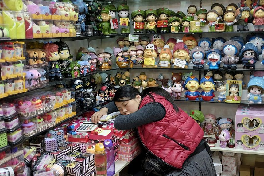 A vendor sleeps at a shop in Beijing, in this Nov 17, 2013 file photo.