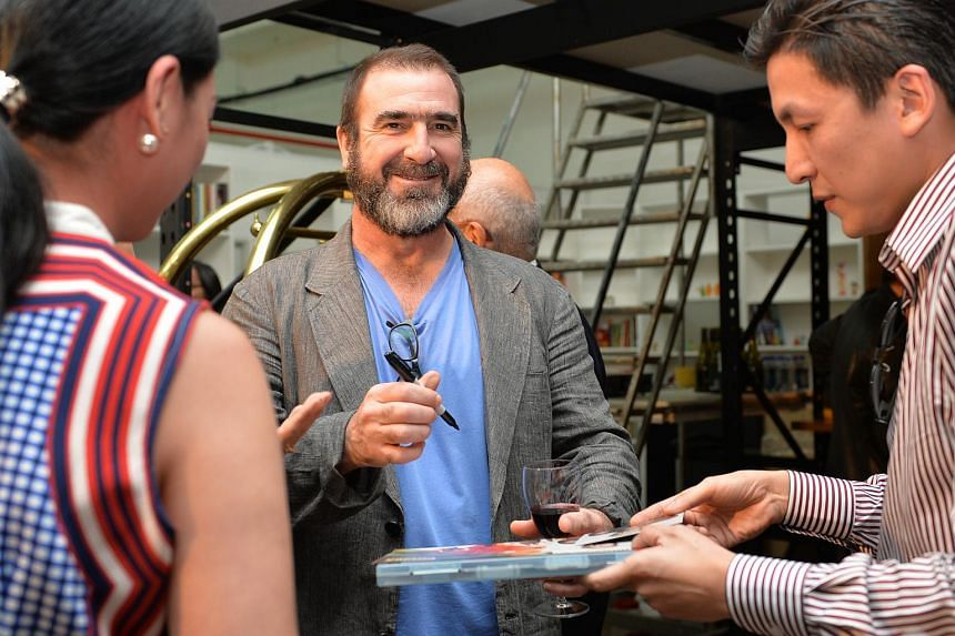Eric Cantona signing his autobiography when he was in Singapore in this Nov 27, 2014 file photo.