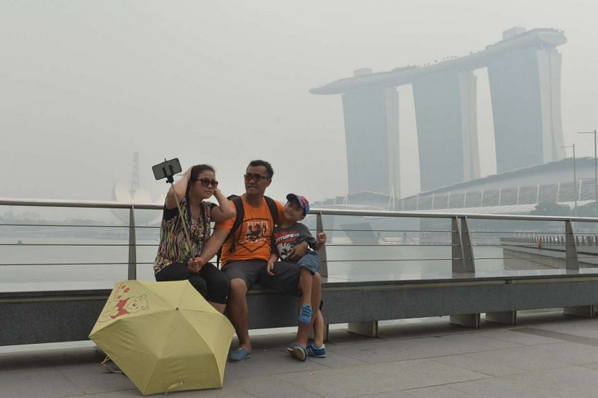 Tourists take photos at the Marina bay area at around 2pm on Sept 22, 2015.