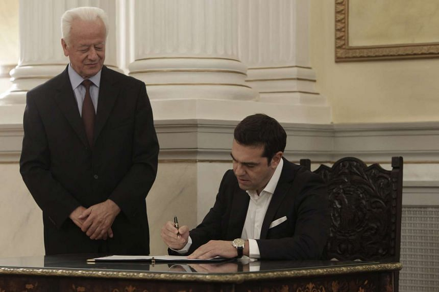 Alexis Tsipras signs documents following his swearing ceremony as Greece's new Prime Minister at the presidential palace in Athens, Greece, on Sept 21, 2015.