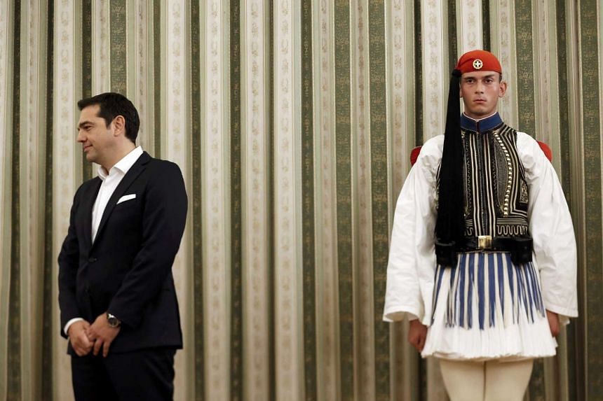 Leftist Syriza leader and winner of Greek general election Alexis Tsipras stands next to a presidential guardsman during a ceremony in which he was sworn in as prime minister at the presidential palace in Athens on Monday.