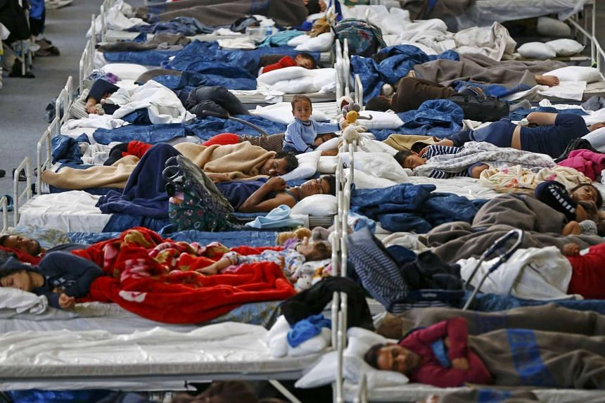 Migrants rest on beds at an improvised temporary shelter in a sports hall in Hanau, Germany.