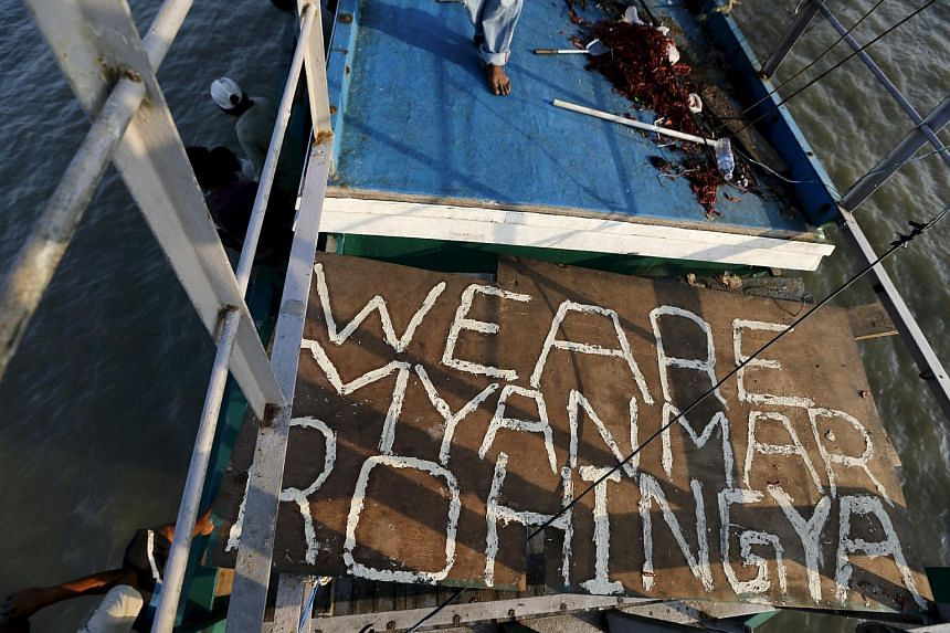 """Plywood with the words """"We are Myanmar Rohingya"""" is seen in an abandoned boat which carried migrants from Thailand in this May 20, 2015 file photo."""